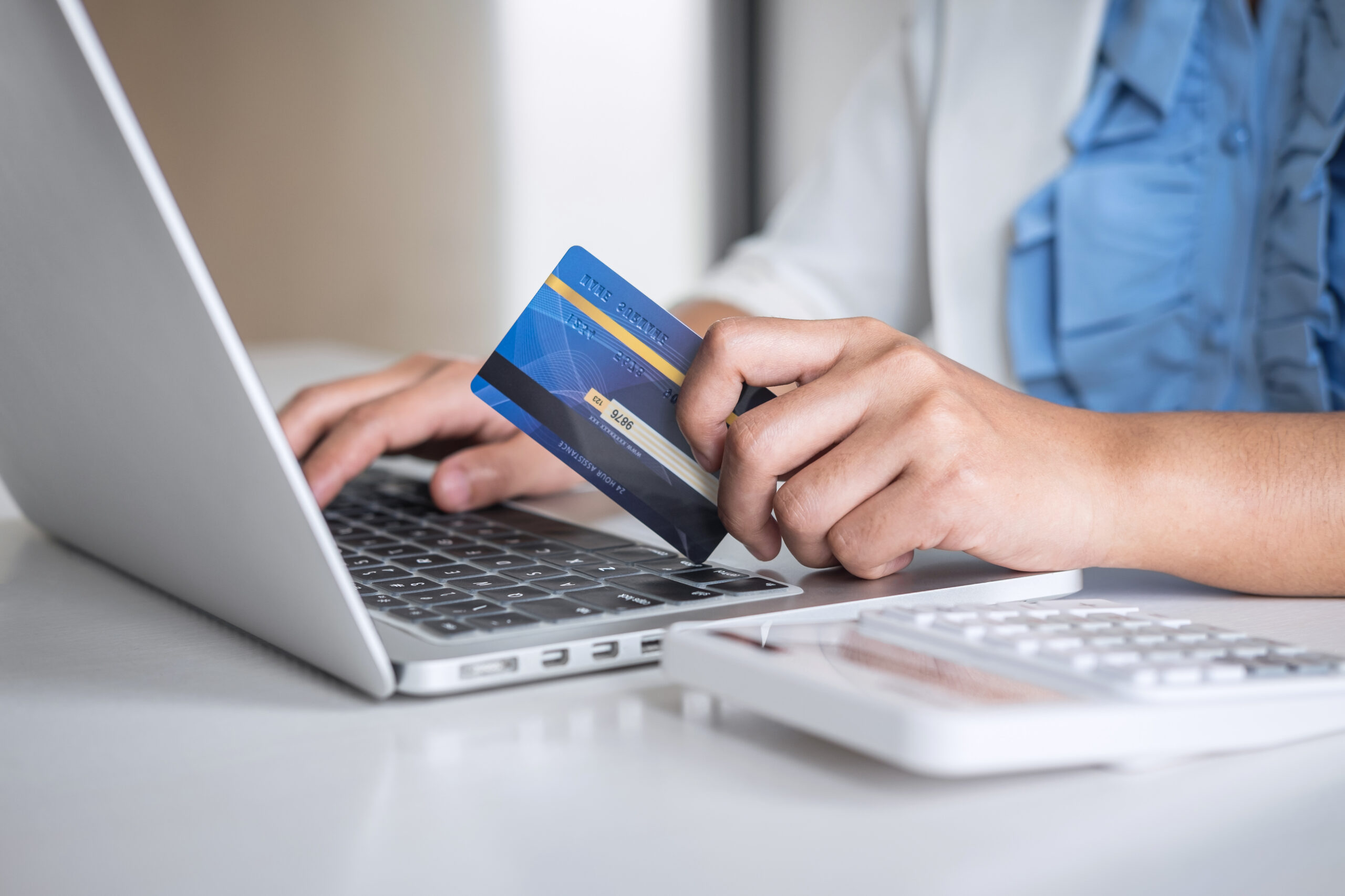 Business woman consumer holding credit card and typing on laptop